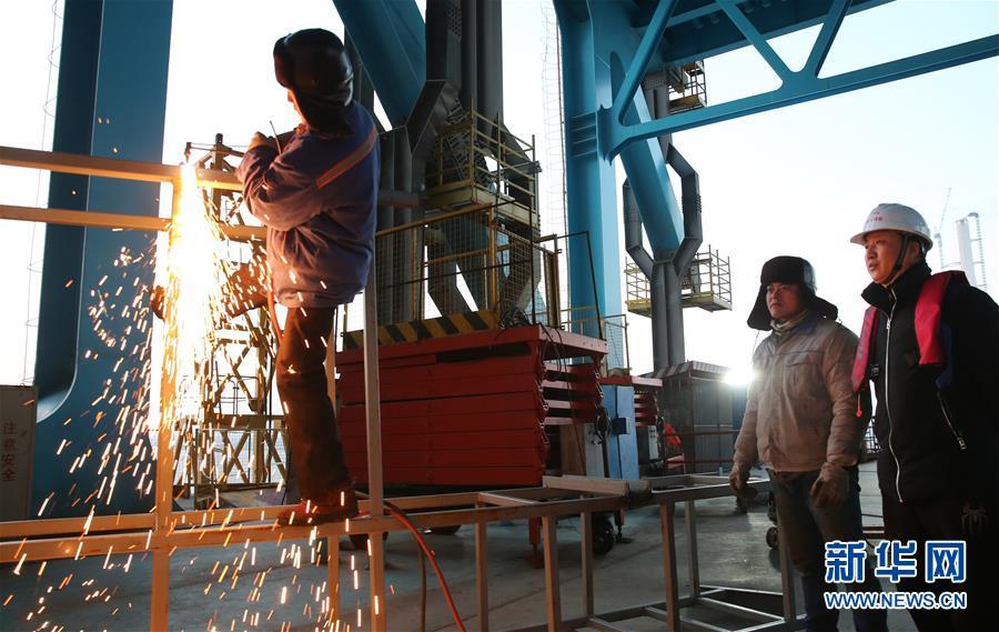 12月28日,顾惠明(右一)在沪通长江大桥29号南主塔一处电焊现场做事。