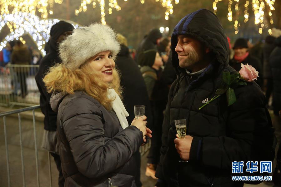 1月1日,在罗马尼亚布添勒斯特,一对情侣在跨年祝贺运动上喝香槟。 新华社发(彼得雷斯库摄)