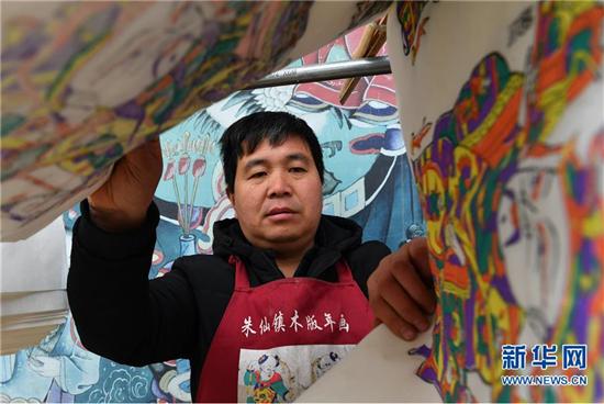 1月8日,在开封市朱仙镇,一位年画艺人将制作好的木版年画拿出晾晒。