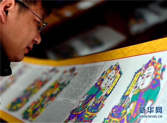 1月8日,在开封市朱仙镇,一位游客在欣赏装裱好的木版年画成品。