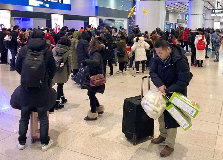 北京南站,返京的搭客携带着各种行李到达。