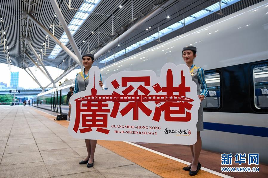 2018年9月23日,广深港高铁全线开通运营,从深圳北站开往香港西九龙站的G5711次高铁列车乘务员展示纪念牌。新华社记者 毛思倩