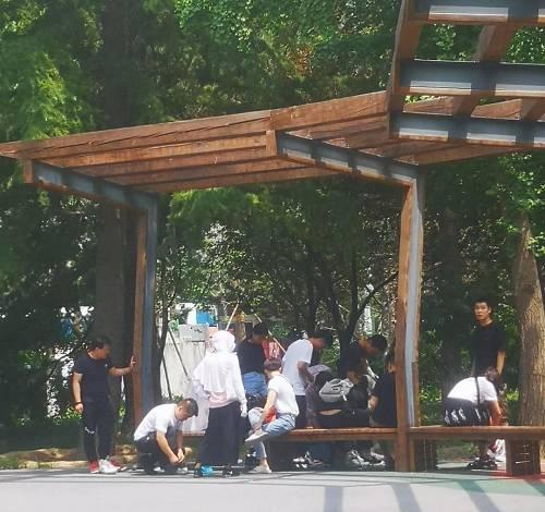 6月15日中午,北京工人体育场小公园内,准备参加抽签活动的人正在换鞋。摄影/熊大志