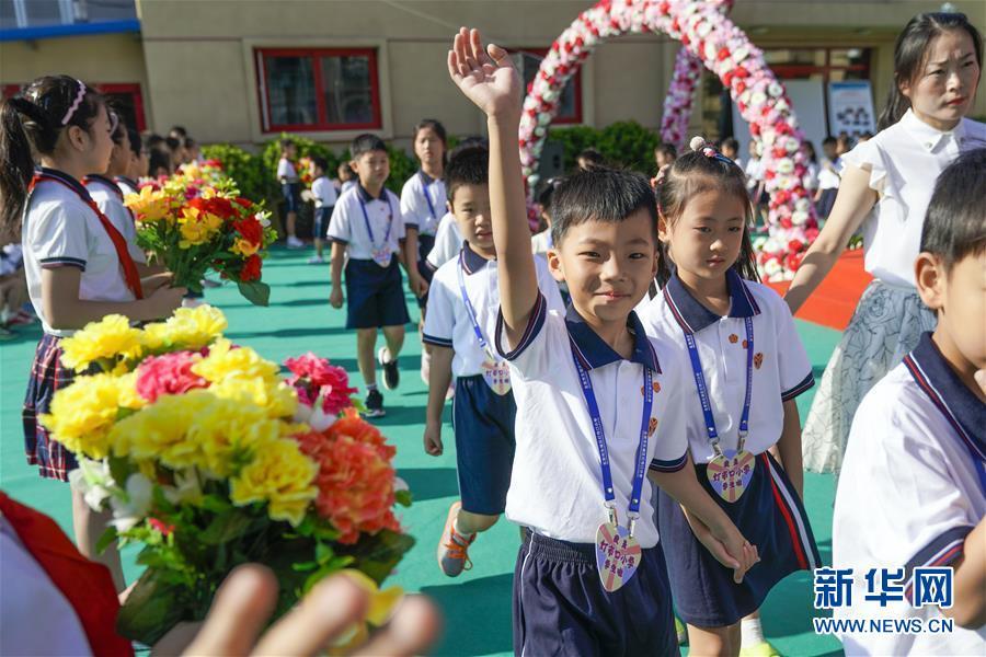 9月1日,在北京市东城区灯市口小学灯市口校区的开学典礼上,一年级新生在老师的带领下步入会场,准备参加开学典礼。新华社记者 沈伯韩