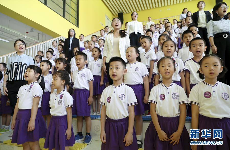 9月1日,新成立的清华大学附属中学广华学校小学部首批152名一年级新生和老师在开学典礼上高唱国歌。新华社记者 丁海涛