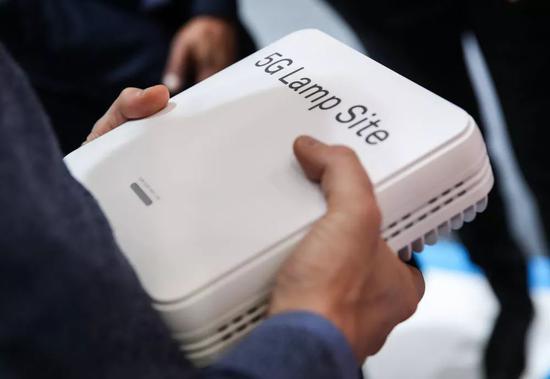 2019年4月3日,在德国汉诺威工博会上,一名参观者手持华为展区展出的一个5G小基站。(新华社记者单宇琦摄)