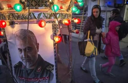 """1月5日,在伊朗首都德暗兰,人们走过悼念伊朗伊斯兰革命卫队属下""""圣城旅""""指挥官苏莱曼尼的海报。新华社"""