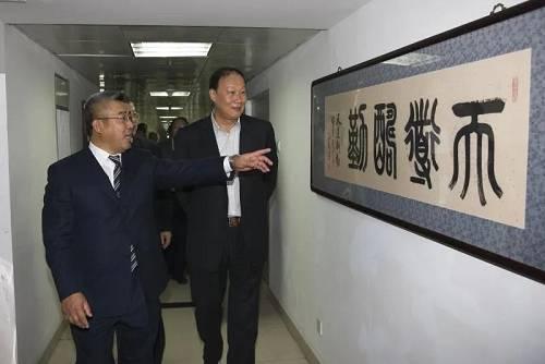 时任国家税务总局党组副书记、副局长钱冠林(右)参观了解公司大事记。