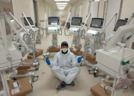 """志愿者杨杰与雷师傅在泰康同济医院通宵安装15台呼吸机。图片转自""""南派纪录片"""""""