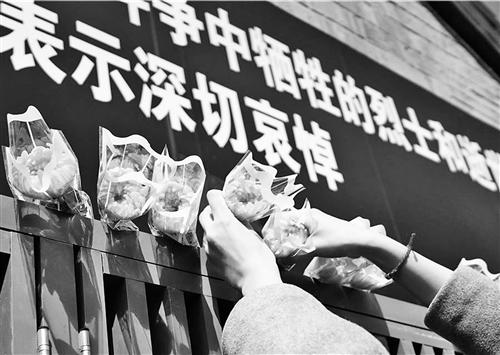 4月4日,北京市前门街道草厂社区,居民们为牺牲烈士和逝世同胞献上鲜花。本报记者 赵 晶摄